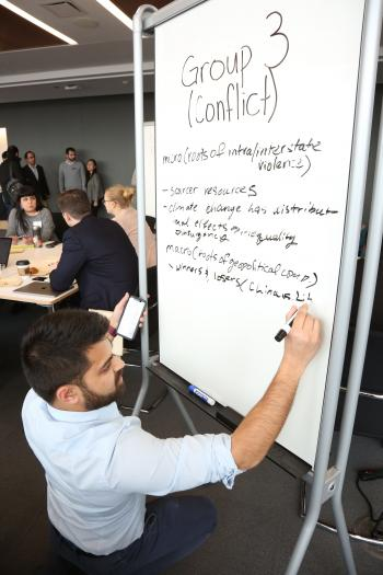 A Harris Public Policy student writes on a whiteboard.